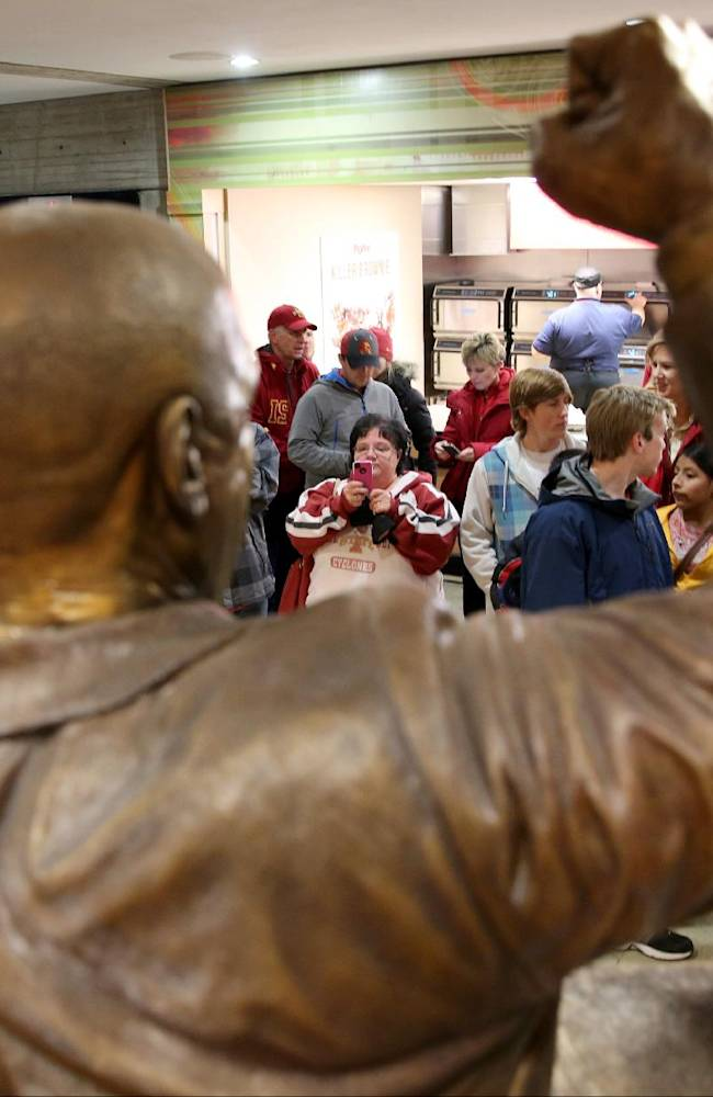 Fans stop by to look at and take pictures of the statue of former Iowa State coach Johnny Orr before Iowa State's NCAA college basketball game against Northern Illinois at Hilton Coliseum in Ames, Iowa., Tuesday, Dec. 31, 2013. Orr, 86, who also coached at Michigan, has died, Iowa State confirmed Tuesday