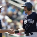 New York Yankees' Francisco Cervelli, right, is greeted by hitting coach Butch Wynegar after scoring on a two-run double by Scott Sizemore in the fourth inning of an exhibition baseball game against the Minnesota Twins in Fort Myers, Fla., Saturday, March