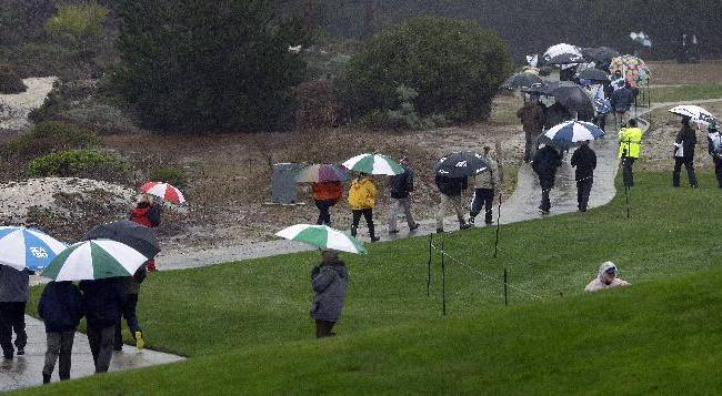 Fans leave the the Spyglass Hill Golf Course Thursday, Feb. 6, 2014, in Pebble Beach, Calif. Play was suspended due to rain