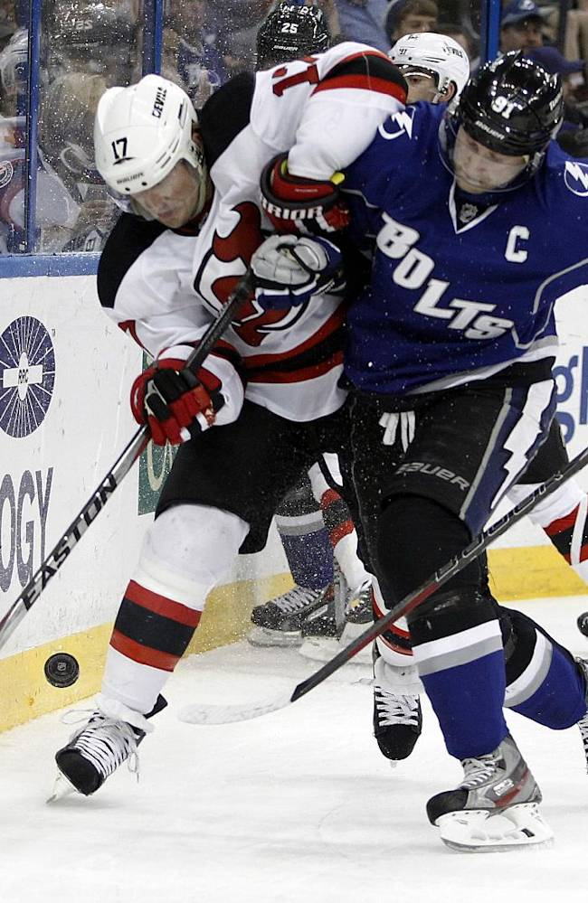 New Jersey Devils right wing Michael Ryder (17) and Tampa Bay Lightning center Steven Stamkos (91) collide as they battle for the puck during the first period of an NHL hockey game Saturday, March 15, 2014, in Tampa, Fla