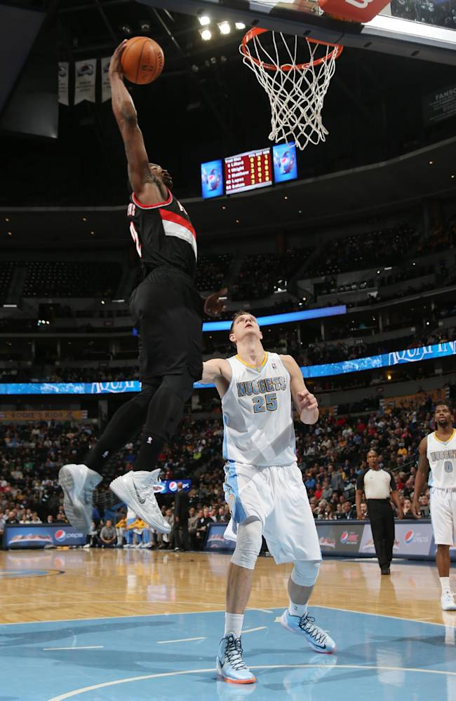 Portland Trail Blazers guard Wesley Matthews, left, flies over Denver Nuggets center Timofey Mozgov, of Russia, to dunk the ball for a basket in the first quarter of an NBA basketball game in Denver, Tuesday, Feb. 25, 2014
