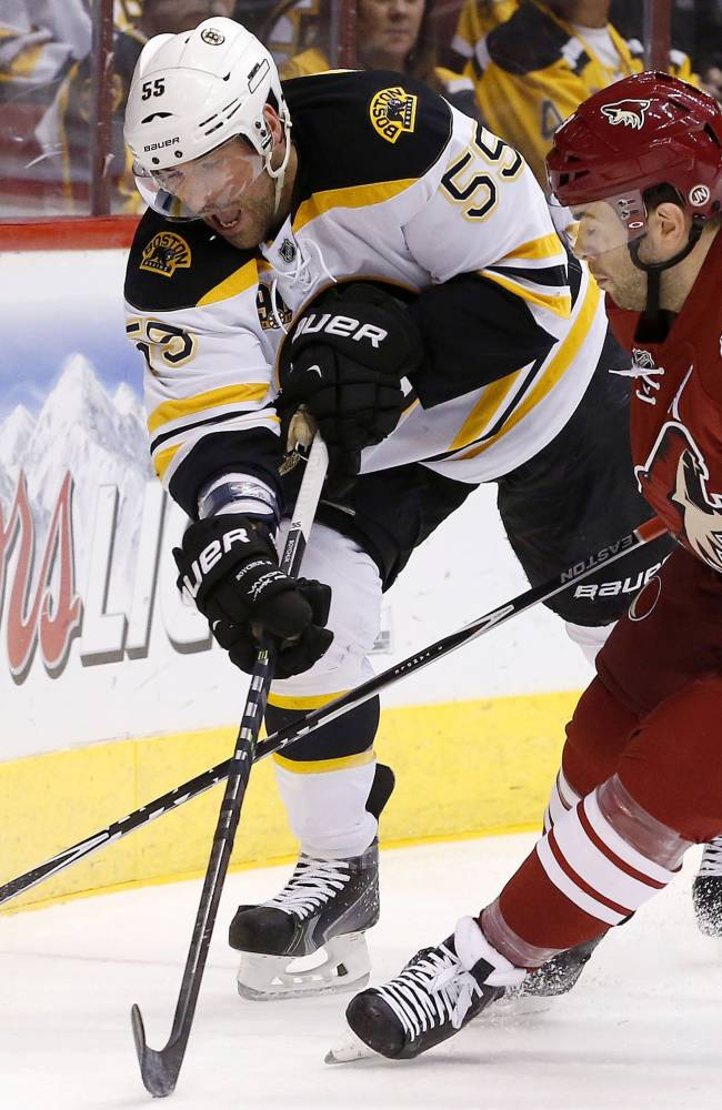 Boston Bruins' Johnny Boychuk (55) and Phoenix Coyotes' Keith Yandle (3) battle for the puck during the first period of an NHL hockey game on Saturday, March 22, 2014, in Glendale, Ariz