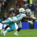 Miami Dolphins' Philip Wheeler, front, and Oakland Raiders' Maurice Jones-Drew reach for the ball during the NFL football game at Wembley Stadium in London, Sunday, Sept. 28, 2014. The Associated Press