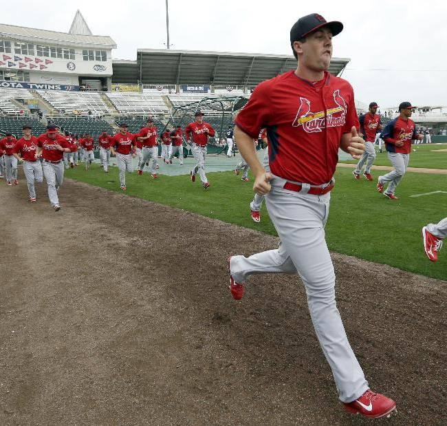 St. Louis Cardinals pitcher Tim Cooney, front, warms up with teammates before an exhibition baseball game against the Minnesota Twins, Thursday, March 6, 2014, in Fort Myers, Fla