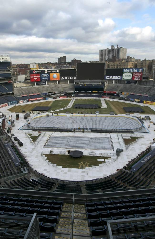 Workers install an outdoor hockey rink on the infield of  New York's Yankee Stadium, Saturday, Jan. 18, 2014 for NHL Stadium Series games. The stadium will host the New York Rangers and New Jersey Devils on Jan. 26 and the Rangers-New York Islanders on Jan. 29