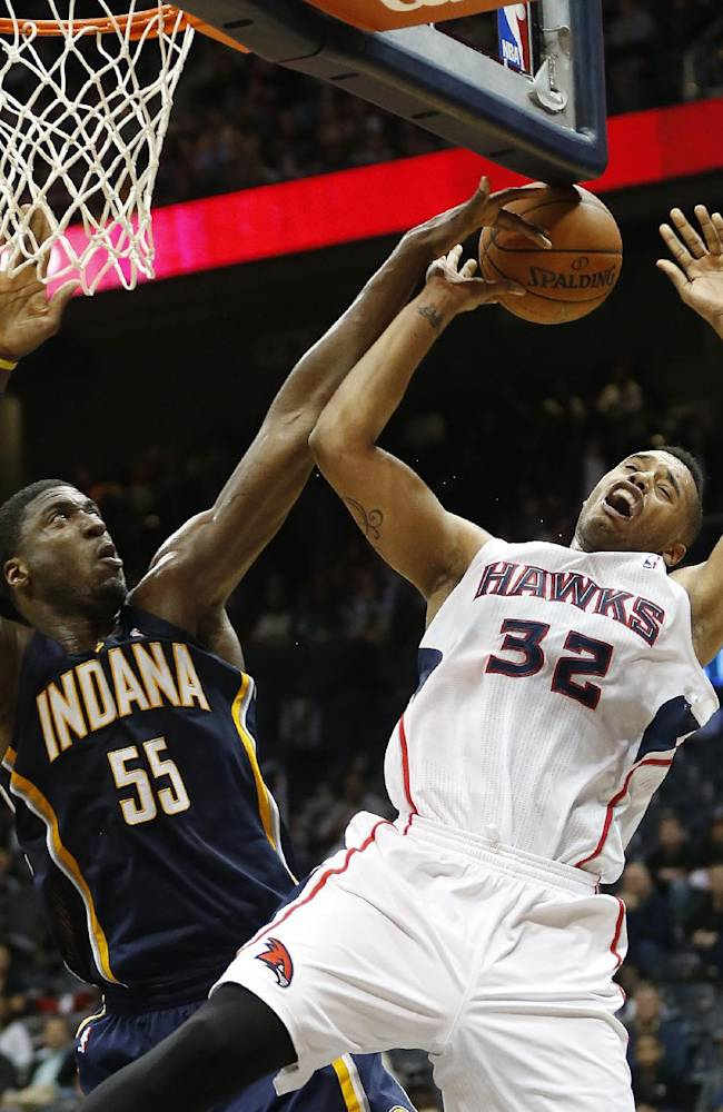 Atlanta Hawks power forward Mike Scott (32) has his shot blocked by Indiana Pacers center Roy Hibbert (55) in the second half of an NBA basketball game, Tuesday, Feb. 4, 2014, in Atlanta. Indiana won 89-85