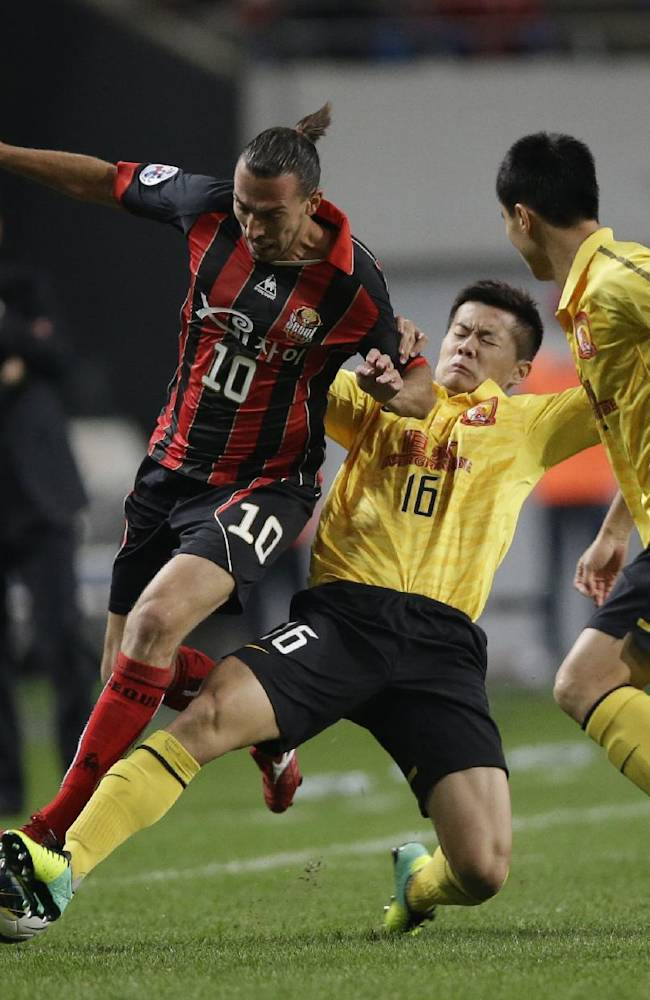 Dejan Damjanovic, left, of South Korea's FC Seoul fights for the ball against Huang Bowen, center, of China's Guangzhou Evergrande during the first leg of the 2013 Asian Champions League final against South Korea's club FC Seoul at Seoul World Cup Stadium in Seoul, South Korea, Saturday, Oct. 26, 2013