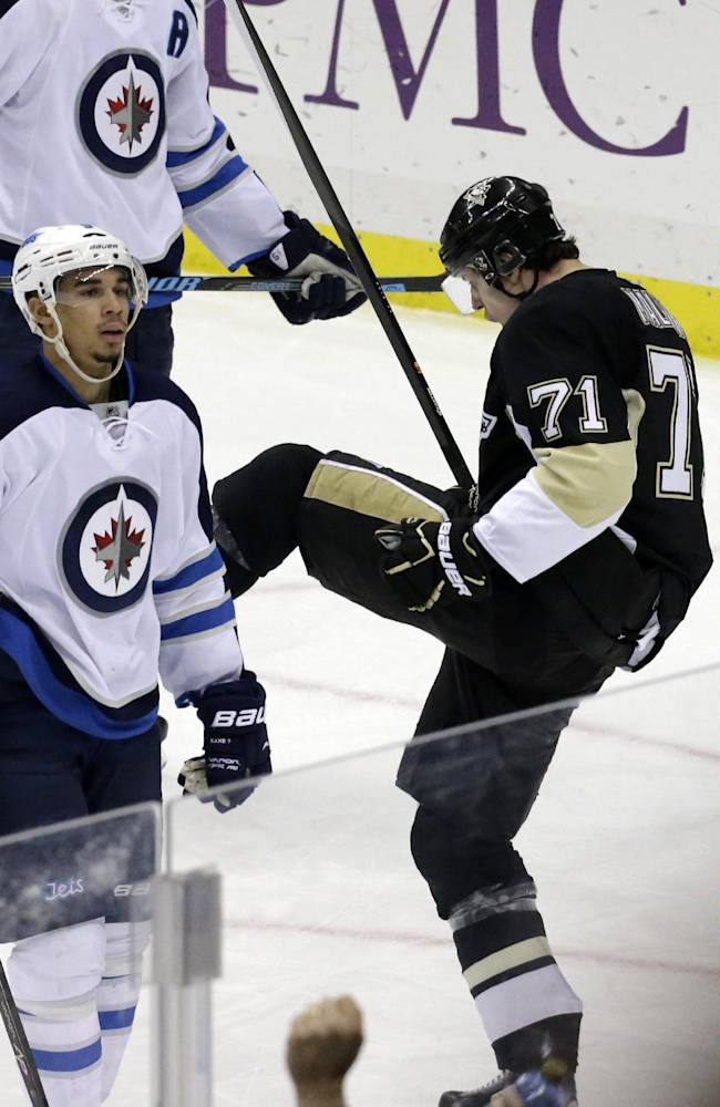 Pittsburgh Penguins' Evgeni Malkin (71) celebrates his goal as Winnipeg Jets' Evander Kane (9) skates back to his bench in the third period of an NHL hockey game in Pittsburgh, Sunday, Jan. 5, 2014. The Penguins won 6-5