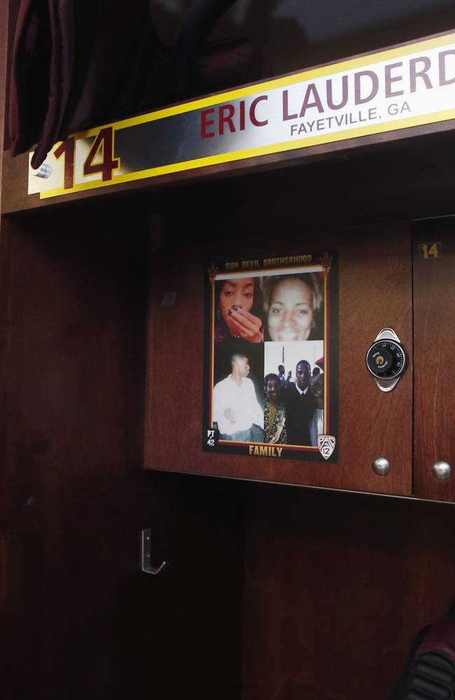 Arizona State's Eric Lauderdale has a photo of his late parents along with his grandmother and sister attached to his locker in the Arizona State football team locker room Monday, Aug. 11, 2014, in Tempe, Ariz.  Each player and coach on Arizona State's team has a photo above their locker of someone who has inspired them. There are mothers, fathers, siblings, grandparents, a few coaches. Coach Todd Graham had them all do it so they can remember it's not just their teammates they're playing for