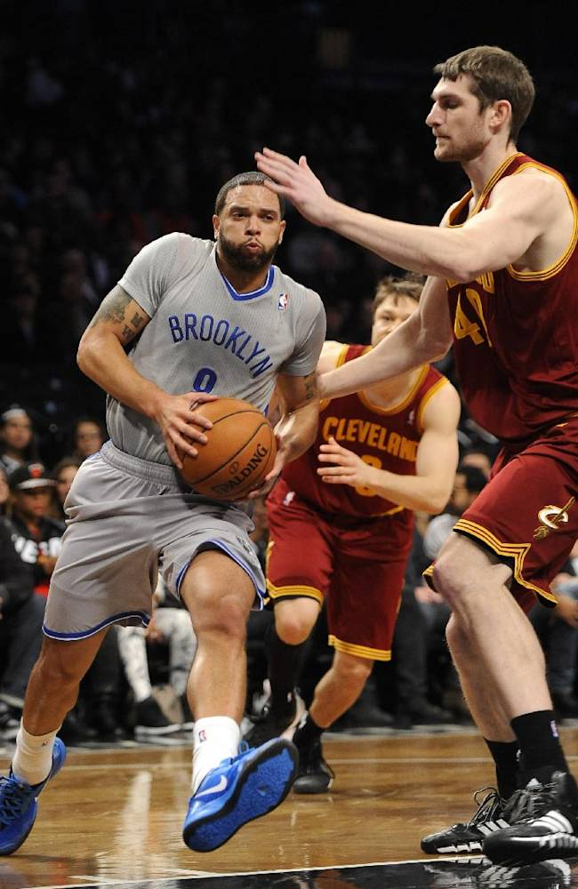 Brooklyn Nets' Deron Williams (8) drives the ball to the basket against Cleveland Cavaliers' Tyler Zeller (40) during the first half of an NBA basketball game Friday, March 28, 2014, in New York. The Nets won 108-97