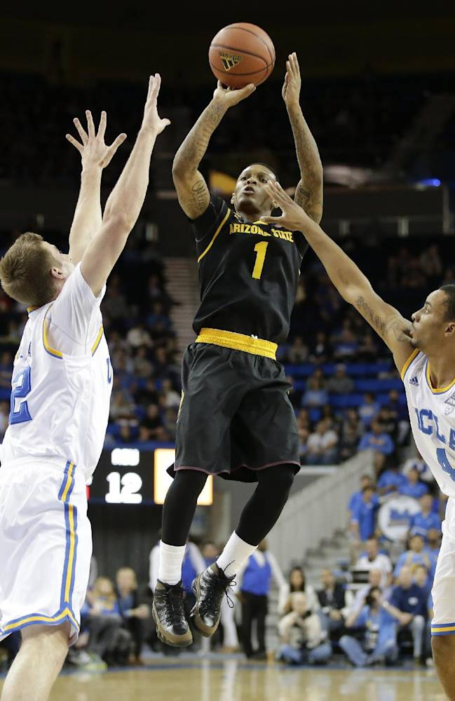 Arizona State guard Jahii Carson, middle, shoots between UCLA forward David Wear, left, and guard Norman Powell during the first half of an NCAA college basketball game in Los Angeles, Sunday, Jan. 12, 2014