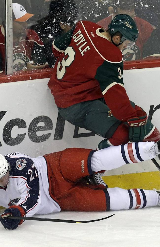 Minnesota Wild's Charlie Coyle, top, topples over Columbus Blue Jackets' Ryan Murray in a collision along the boards in the first period of a NHL preseason hockey game, Tuesday, Sept. 17, 2013 in St. Paul. Minn