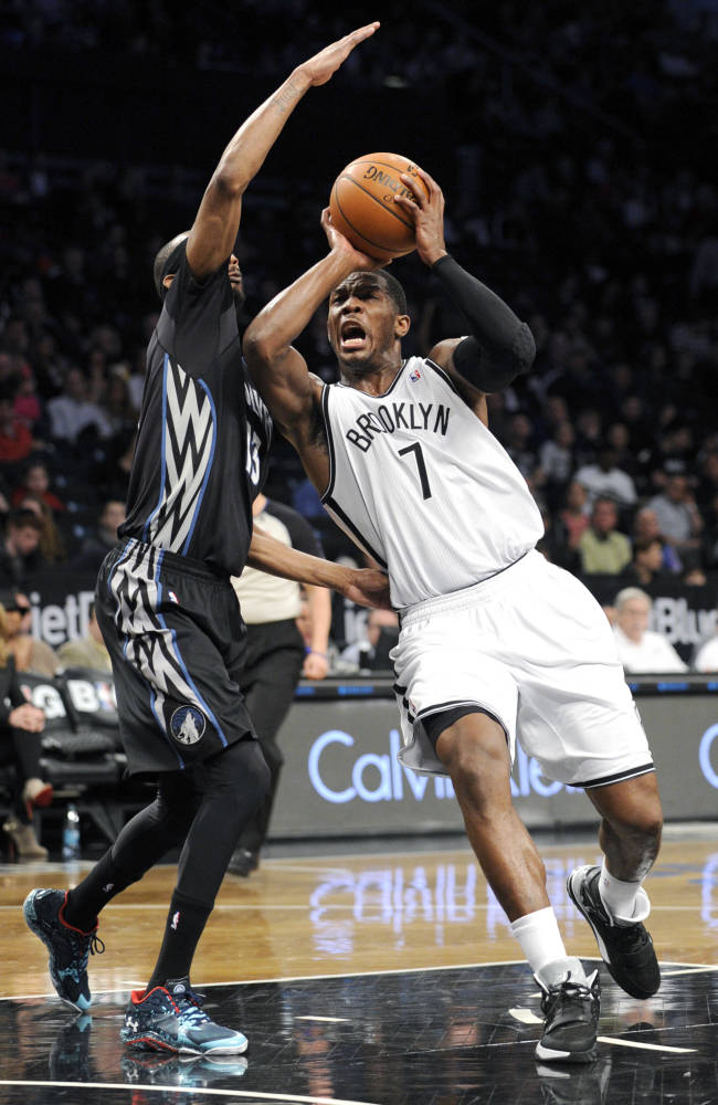 Brooklyn Nets' Joe Johnson (7) drives to the basket as he guarded by Minnesota Timberwolves' Corey Brewer during the first quarter of an NBA basketball game on Sunday, March 30, 2014, at Barclay's Center in New York. (AP Photo/Bill Kostroun)