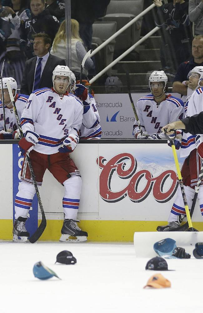 The New York Rangers watch from the sideline as hats thrown on the ice by fans are picked up following San Jose Sharks' Tomas Hertl, of the Czech Republic's third goal of the game during the third period of an NHL hockey game on Tuesday, Oct. 8, 2013, in San Jose, Calif