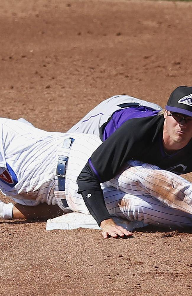 Colorado Rockies' Josh Rutledge, right, lands on Chicago Cubs' Darwin Barney, left, after forcing him out at second base during the third inning of a spring training baseball game on Tuesday, March 11, 2014, in Mesa, Ariz. The Rockies defeated the Cubs 13-0