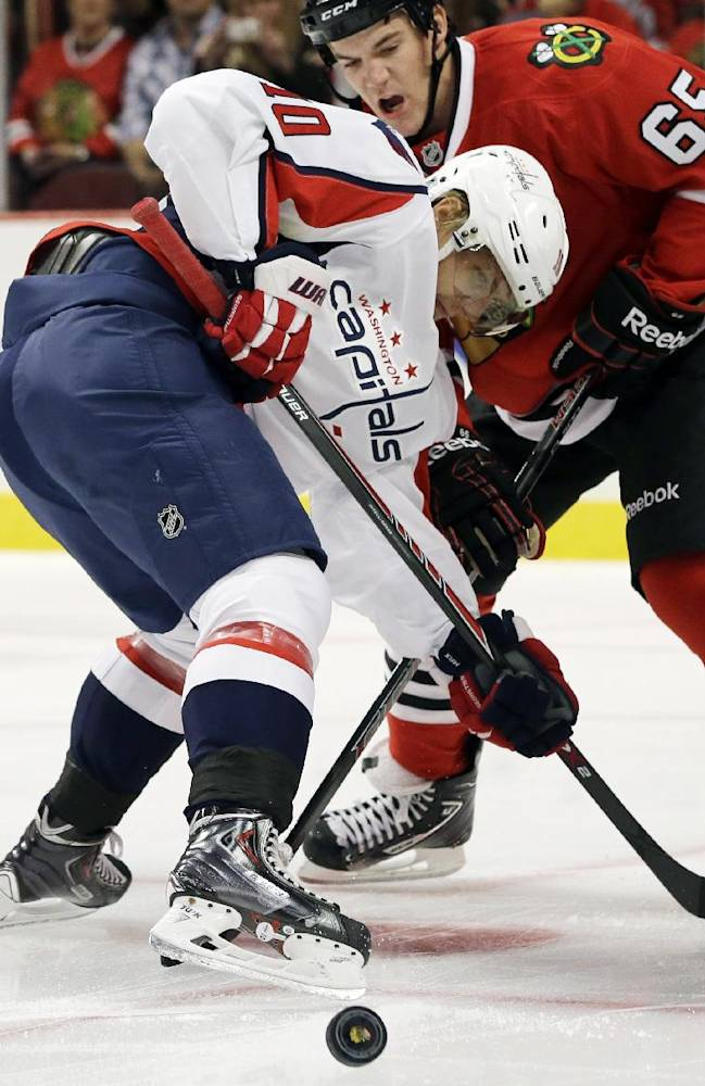 Washington Capitals' Martin Erat (10) battles for the puck against Chicago Blackhawks' Andrew Shaw (65)  during the first period of an NHL preseason hockey game in Chicago, Saturday, Sept. 28, 2013