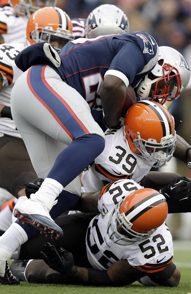 Cleveland Browns safety Tashaun Gipson (39) and linebacker D'Qwell Jackson (52) tackle New England Patriots running back LeGarrette Blount (29) in the first quarter of an NFL football game on Sunday, Dec. 8, 2013, in Foxborough, Mass