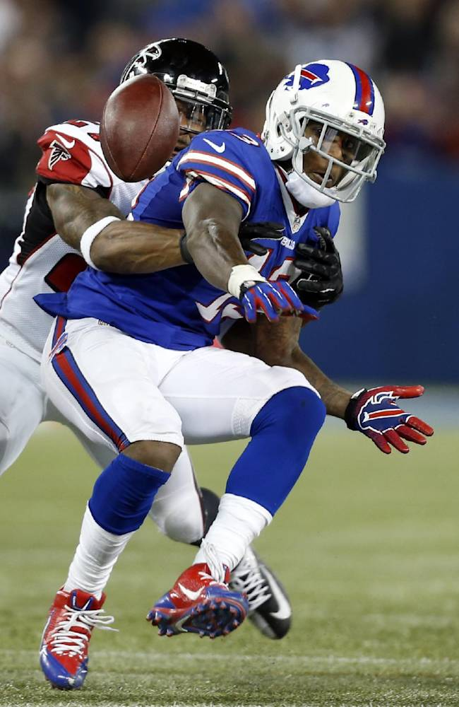 Buffalo Bills wide receiver Stevie Johnson (13) fumbles as he is tackled by Atlanta Falcons cornerback Robert McClain (27) during the second half of an NFL football game on Sunday, Dec. 1, 2013, in Toronto