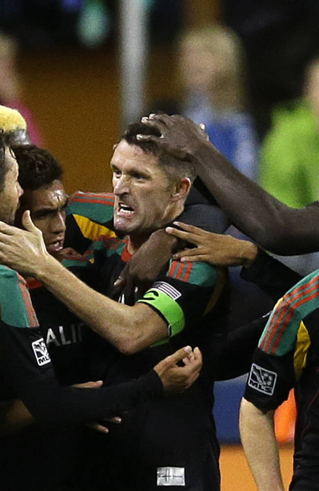 Los Angeles Galaxy's Robbie Keane, center, celebrates with teammates after he scored a goal against the Seattle Sounders in the second half of an MLS soccer match, Sunday, Oct. 27, 2013, in Seattle. The Sounders and the Galaxy tied 1-1