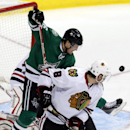 Dallas Stars left wing Ryan Garbutt, center, jumps as he tries to get the puck in the goal as Chicago Blackhawks defenseman Nick Leddy (8) defends during the third period of an NHL hockey game Saturday, Nov. 9, 2013, in Dallas, Texas The Associated Press