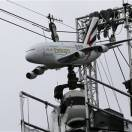 An advertising model of an A380 Airbus of Emirates airline is set up to carry an overhead  broadcast camera  for the 2013 French Open tennis tournament, at Roland Garros stadium in Paris, Friday May, 24, 2013. (AP Photo/Christophe Ena)