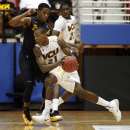 VCU forward Treveon Graham, front, drives to the basket against Long Beach guard Mike Caffey at a NCAA college basketball game in San Juan, Puerto Rico, Friday, Nov. 22, 2013. (AP Photo/Ricardo Arduengo)
