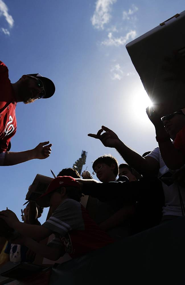 Washington Nationals' Adam LaRoche, left, signs autographs for fans before the start an exhibition spring training baseball game against the Miami Marlins, Saturday, March 15, 2014, in Jupiter, Fla