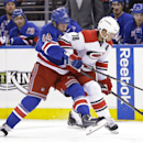 New York Rangers defenseman Matt Hunwick (44) and Carolina Hurricanes' Jay McClement (18) fight for control of the puck during the first period of an NHL hockey game Thursday, Oct. 16, 2014, in New York The Associated Press