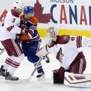 Arizona Coyotes goalie Devan Dubnyk (40) makes the save as Keith Yandle (3) and Edmonton Oilers Mark Arcobello (26) battle in front during first period NHL hockey action in Edmonton, Alberta, on Sunday, Nov. 16, 2014 The Associated Press
