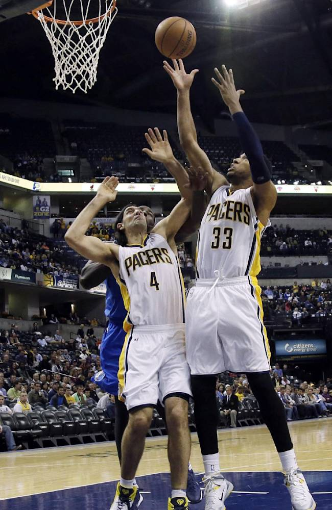 Indiana Pacers forward Danny Granger (33) pulls down a rebound in front of teamate Luis Scola (4) during the first half of an NBA preseason basketball game against the Dallas Mavericks in Indianapolis, Wednesday, Oct. 16, 2013. Granger left the game with 4:05 left in the first quarter with a strained left calf and did not return. The Mavericks won 92-85