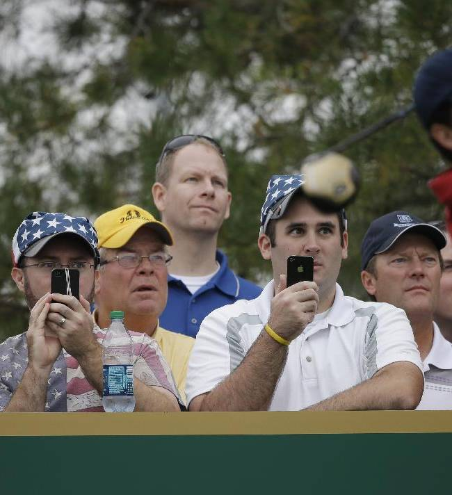Fans take photos with cell phones as United States team player Keegan Bradley tees of the 11th hole during a practice round for the Presidents Cup golf tournament at Muirfield Village Golf Club Wednesday, Oct. 2, 2013, in Dublin, Ohio