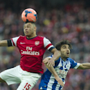 Arsenal's Alex Oxlade-Chamberlain, left, fights for the ball with Wigan Athletic's James Perch during their English FA Cup semifinal soccer match, at the Wembley Stadium in London, Saturday, April 12, 2014