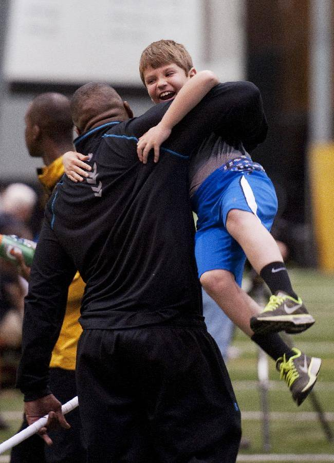 Missouri defensive lineman Michael Sam, left, picks up Andrew Hill as he greets him during pro day for NFL football representatives Thursday, March 20, 2014, in Columbia, Mo. Hill is the son of associate head coach Andy Hill