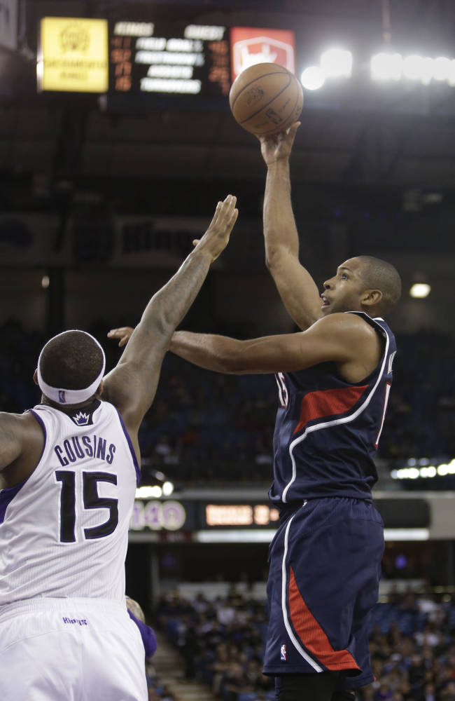Atlanta Hawks center Al Horford, right shoots over Sacramento Kings center DeMarcus Cousins during the fourth quarter of an NBA basketball game in Sacramento, Calif., Tuesday, Nov. 5, 2013.  The Hawks won 105-100