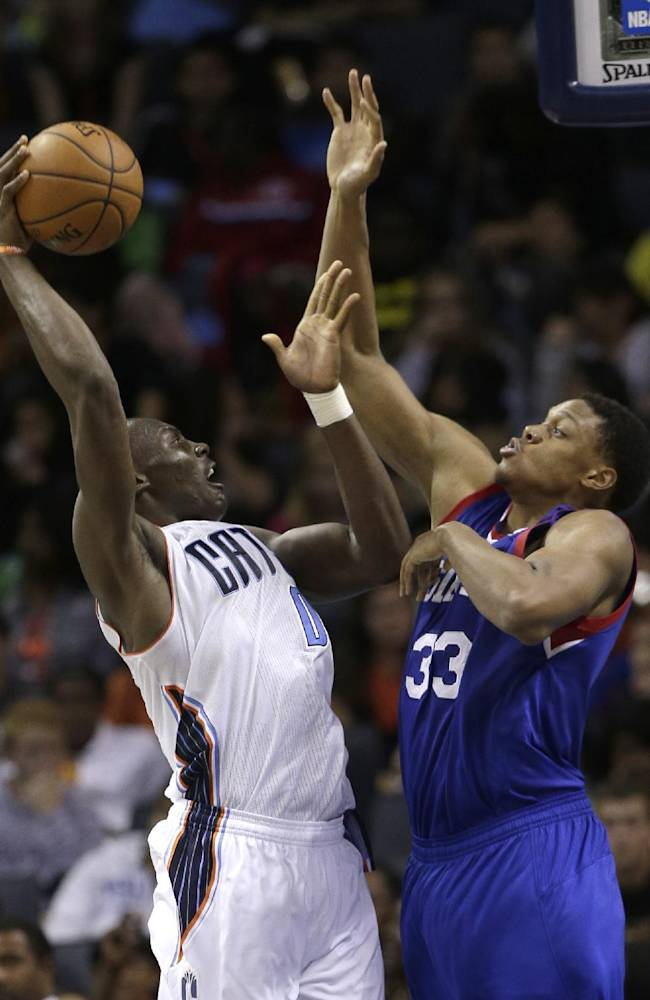 Charlotte Bobcats' Bismack Biyombo (0) shoots over Philadelphia 76ers' Daniel Orton (33) during the second half of a preseason NBA basketball game in Charlotte, N.C., Thursday, Oct. 17, 2013. The Bobcats won 110-84
