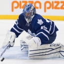 Toronto Maple Leafs goaltender Jonathan Bernier covers the puck after making a save against the Columbus Blue Jackets during the first period of an NHL hockey game Friday, Jan. 9, 2015, in Toronto The Associated Press