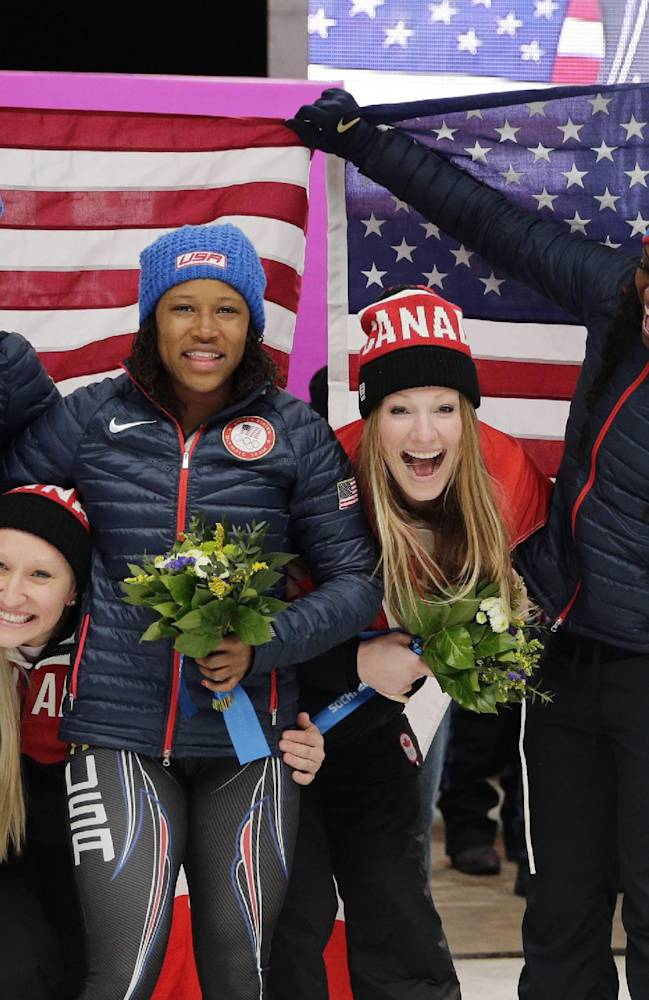 Gold medal winners from Canada Kaillie Humphries and Heather Moyse, poke their heads under the flag as silver medal winners from the United States Elana Meyers and Lauryn Williams, and bronze medal winners from the United States Jamie Greubel and Aja Evans pose for pictures after the women's bobsled competition at the 2014 Winter Olympics, Wednesday, Feb. 19, 2014, in Krasnaya Polyana, Russia. (AP Photo/Jae C. Hong)