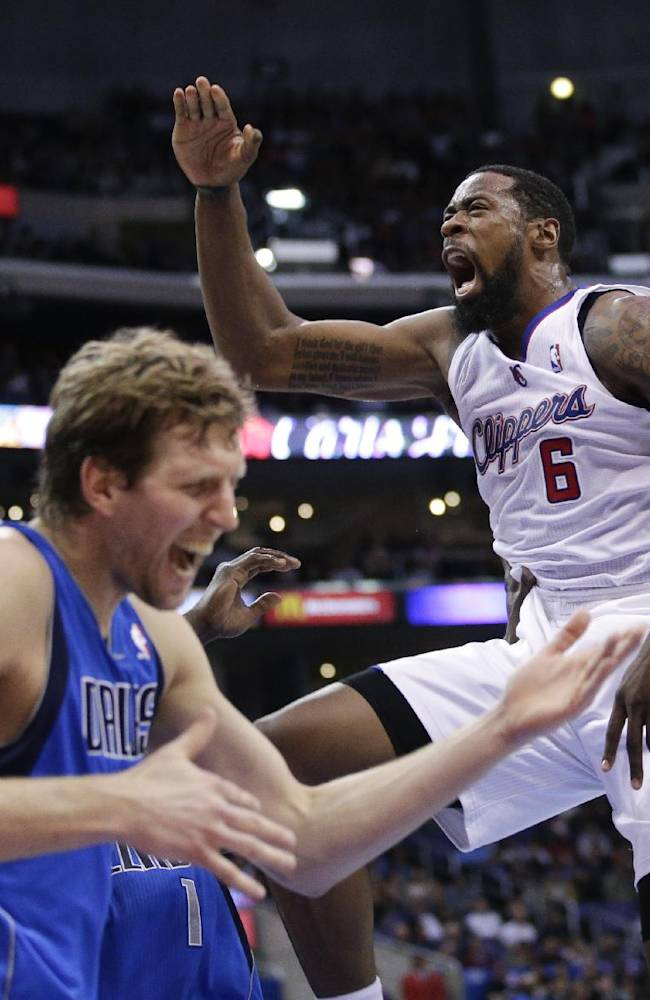 Los Angeles Clippers' DeAndre Jordan, right, screams after making a dunk in front of Dallas Mavericks' Dirk Nowitzki during the first half of an NBA basketball game Thursday, April 3, 2014, in Los Angeles
