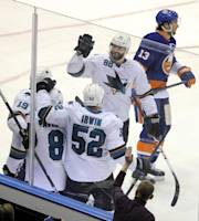 San Jose Sharks' Brent Burns (88) skates in to celebrate Joe Thornton's (19) goal with Joe Pavelski (8) and Matt Irwin (52) as New York Islanders' Colin McDonald (13) skates away in the second period of an NHL hockey game on Friday, March 14, 2014, in Uniondale, N.Y. (AP Photo/Kathy Kmonicek)