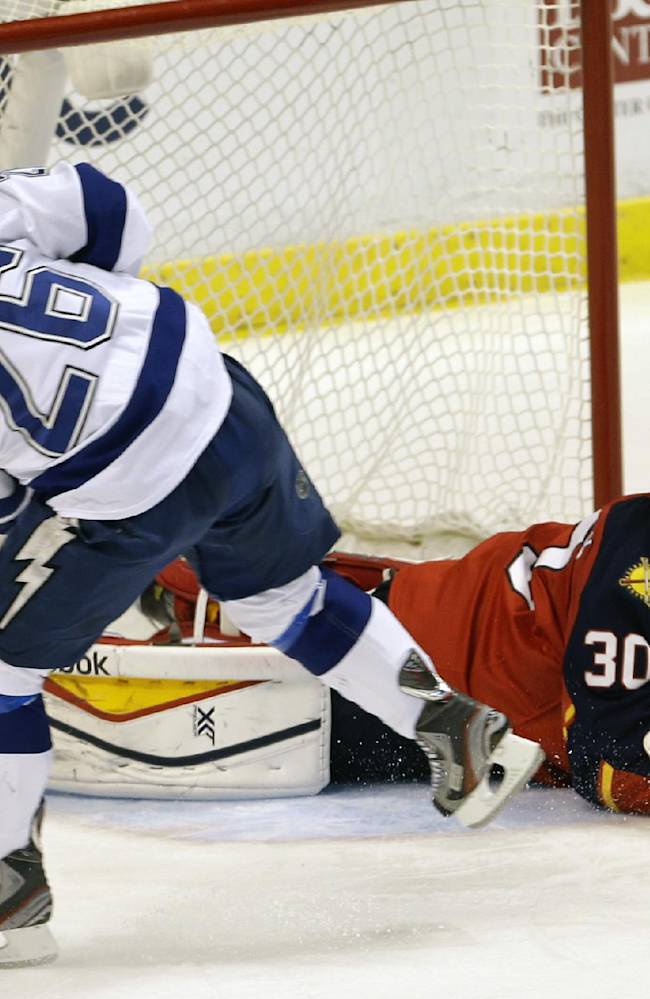 Tampa Bay Lightning right wing Martin St. Louis (26) shoots against Florida Panthers goalie Scott Clemmensen (30) during the second period of an NHL hockey game in Sunrise, Fla., Monday, Dec. 23, 2013. Clemmensen blocked the puck