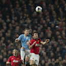 Manchester United's Michael Carrick, right, fights for the ball against Manchester City's Edin Dzeko during their English Premier League soccer match at Old Trafford Stadium, Manchester, England, Tuesday March 25, 2014