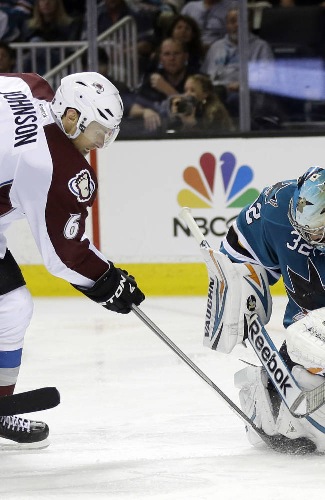 San Jose Sharks goalie Alex Stalock, right, stops a shot from Colorado Avalanche's Erik Johnson (6) during the second period of an NHL hockey game on Friday, April 11, 2014, in San Jose, Calif