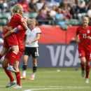 England's Laura Bassett (6) jumps into the arms of Steph Houghton after England defeated Germany 1-0 in the FIFA Women's World Cup third-place soccer match in Edmonton, Alberta, Canada, on Saturday, July 4, 2015. (Jeff McIntosh/The Canadian Press via AP)