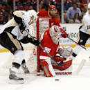 Detroit Red Wings goalie Jimmy Howard (35) stops a Pittsburgh Penguins' Pascal Dupuis (9) shot in the first period of a NHL preseason hockey game in Detroit Wednesday, Oct. 1, 2014 The Associated Press