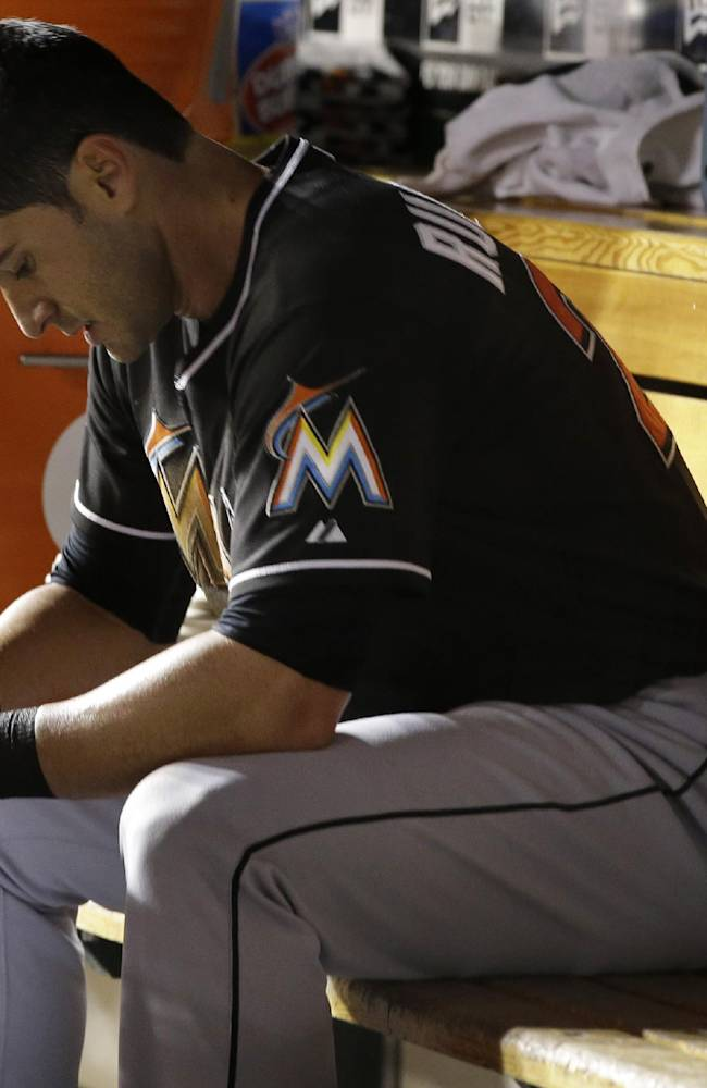 Miami Marlins Justin Ruggiano sits in the dugout after being put out at second base after attempting to steal third during the sixth inning of a baseball game against the Washington Nationals at Nationals Park in Washington, Thursday, Sept. 19, 2013