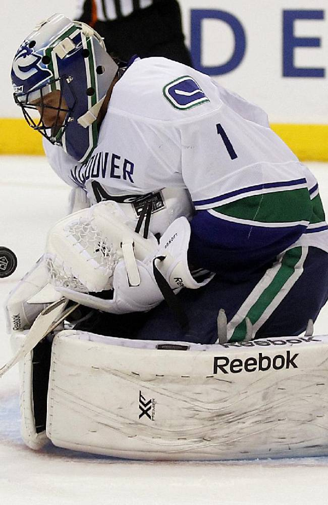 Vancouver Canucks goalie Roberto Luongo (1) makes a stop on a shot by Los Angeles Kings the during the second period of an NHL hockey game Saturday, Jan. 4, 2014, in Los Angeles