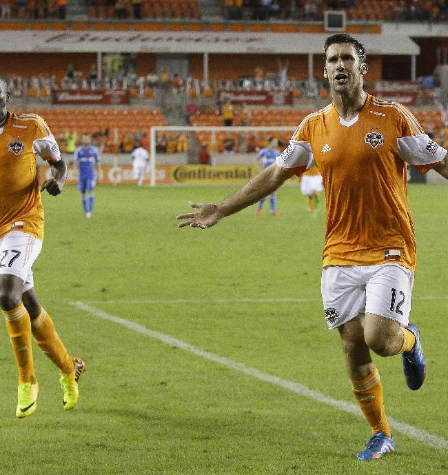 Houston Dynamo forward Will Bruin (12) celebrates his second goal of the game, with midfielder Boniek Garcia (27), against the Montreal Impact during a knockout-round match in the MLS Cup soccer playoffs, Thursday, Oct. 31, 2013, in Houston. Houston won 3-0