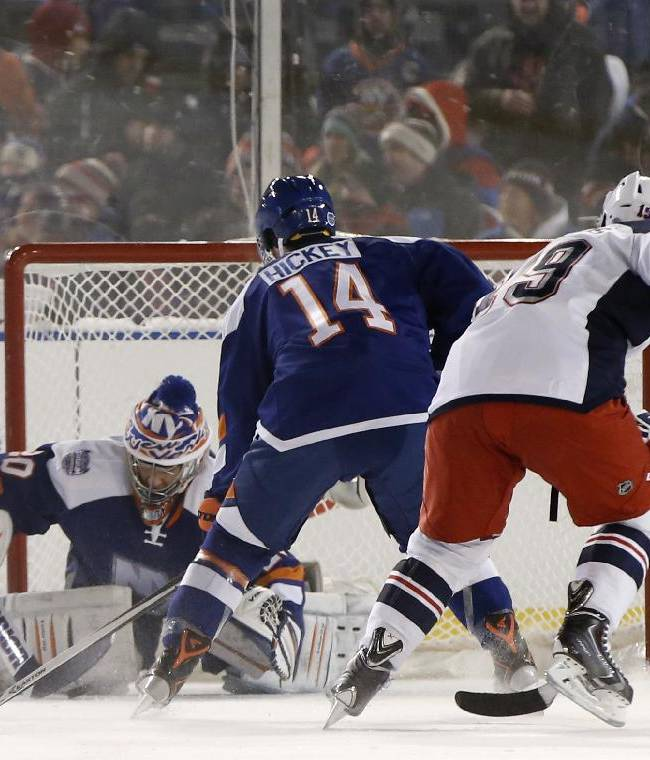 New York Islanders goalie Evgeni Nabokov (20) makes a save as New York Islanders defenseman Thomas Hickey (14) defends against New York Rangers center Brad Richards (19) during the first period of an outdoor NHL hockey game at Yankee Stadium in New York, Wednesday, Jan. 29, 2014