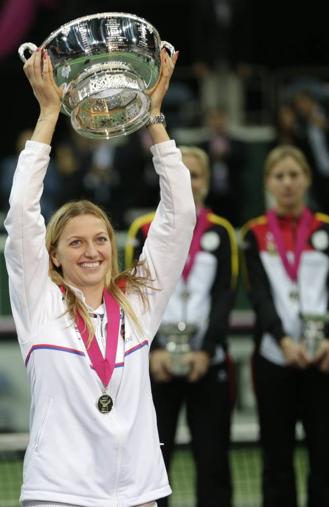 Czech Republic's Petra Kvitova celebrates with the trophy during the awarding ceremony after defeating Germany in their Fed Cup Final tennis match in Prague, Czech Republic, Sunday, Nov. 9, 2014