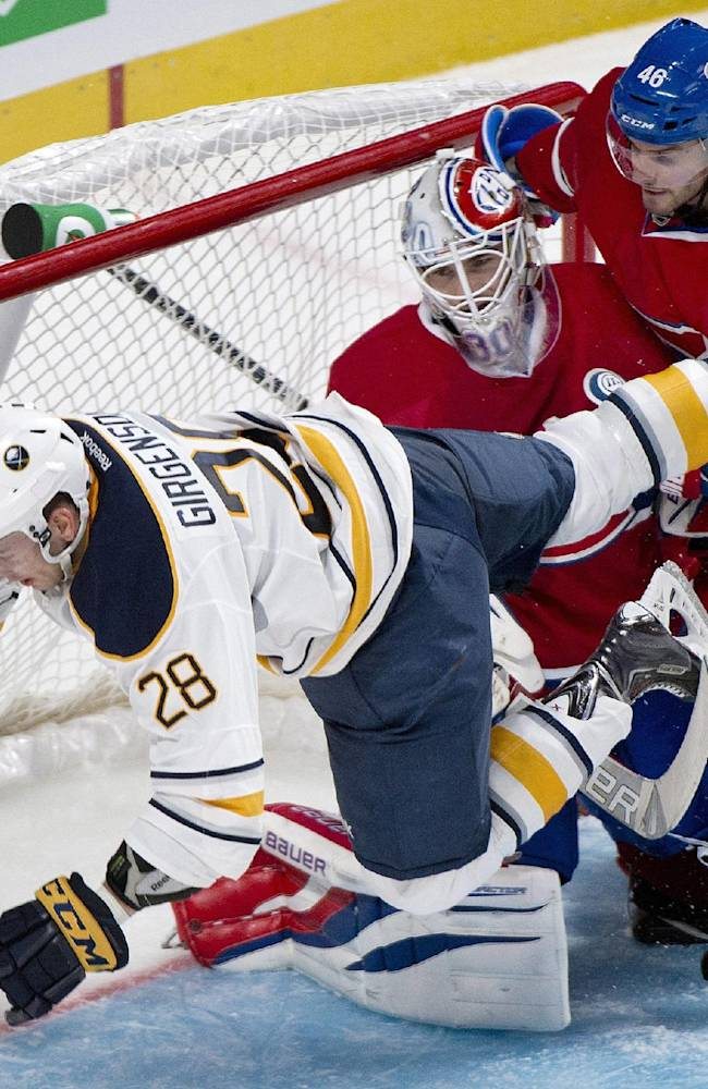 Buffalo Sabres' Zemgus Girgensons (28) collides with Montreal Canadiens' goaltender Peter Budaj, center, as Canadiens' Matt Lashoff defends during the second period of an NHL pre-season hockey game, Sunday, Sept. 15, 2013 in Montreal